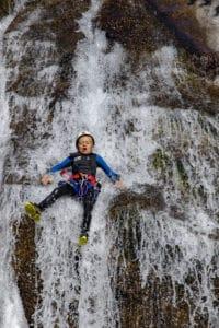 toboggan sur une chute d'eau en canyoning
